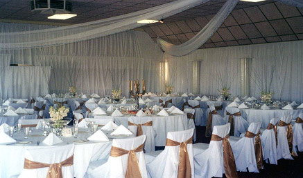 Large function room set up for a wedding reception with white drapery on walls, white tablecoths on tables, white chair covers and floral arrangements on tables